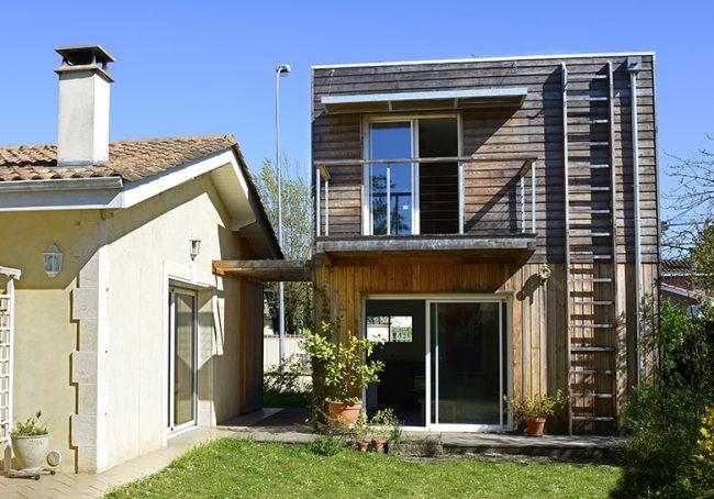 Extension bois à toit plat pour agrandir cette maison bèglaise
