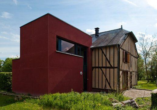 Extension rouge moderne sur maison à colombages